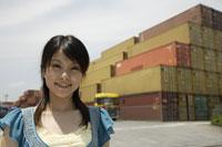 コンテナの前に立つ日本人女性