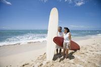 サーフボードを持って海辺に立つシニア夫婦