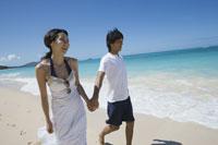 海辺を歩く日本人カップル