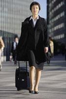 キャリーバッグを引くビジネスウーマン 11019016376| 写真素材・ストックフォト・画像・イラスト素材|アマナイメージズ