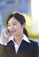 携帯電話で話すビジネスウーマン 11019016387| 写真素材・ストックフォト・画像・イラスト素材|アマナイメージズ