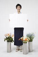 メッセージボードを持つ花屋の女性