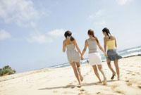 海辺を歩く3人の女性
