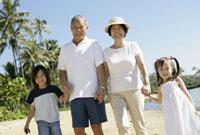 海辺を歩く祖父母と孫