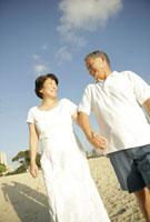 海辺を歩くシニア夫婦