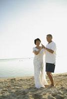砂浜でダンスをするシニア夫婦