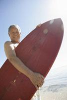 サーフボードを持つシニア男性