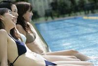 プールサイドに座る3人の女性