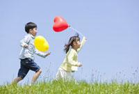 風船を持って土手を走る子供