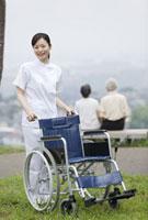 車椅子を押す女性介護士とシニア夫婦