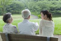 ベンチに座るシニア夫婦と孫の後姿
