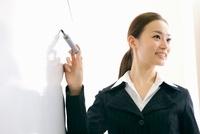 ホワイトボードの前でプレゼンをするビジネスウーマン 11019024373| 写真素材・ストックフォト・画像・イラスト素材|アマナイメージズ