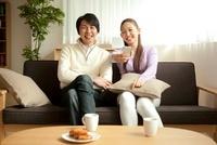 スマートフォンでリモコン操作をしてテレビを見る夫婦 11019025129| 写真素材・ストックフォト・画像・イラスト素材|アマナイメージズ