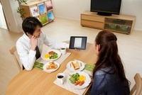 朝食を食べながらのタブレットPC画面を見る夫婦 11019025177| 写真素材・ストックフォト・画像・イラスト素材|アマナイメージズ
