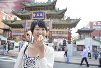 中華街で肉まんを食べてる女性