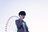 スマートフォンで話すビジネススタイルの女性と観覧車 11019030219| 写真素材・ストックフォト・画像・イラスト素材|アマナイメージズ