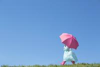 レインコートを着てピンクの傘をさして歩く女の子