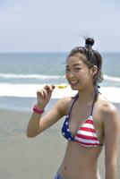 海辺でアイスを食べる水着女性