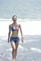 波打ち際を歩く水着女性