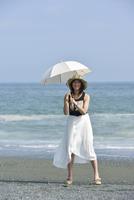 海辺で日傘をさす女性