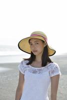 海辺で帽子をかぶる女性