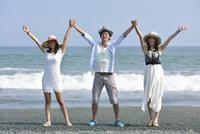 海辺でポーズをとる若者3人