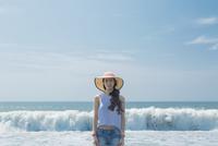 海辺で麦わら帽子をかぶる女性