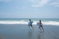 ボディボードを持って波打ち際を走るカップル