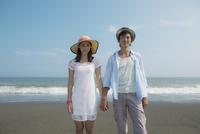 海辺で手をつなぐカップル