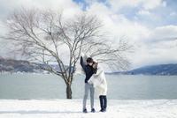 冬の湖畔でブランケットに包まるカップル 11019033514| 写真素材・ストックフォト・画像・イラスト素材|アマナイメージズ