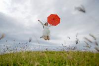 草原で傘を持ってジャンプをする女性