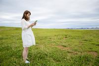 草原でタブレットPCを見る女性