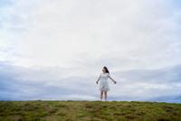 草原で両手を広げて立つ女性