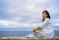 海岸に座って音楽を聴く女性