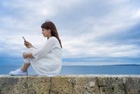 海岸に座ってスマートフォンを見る女性