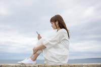 海岸に座って音楽を聴く女性 11019033584| 写真素材・ストックフォト・画像・イラスト素材|アマナイメージズ