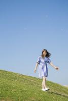 草原を歩く女性 11019033616| 写真素材・ストックフォト・画像・イラスト素材|アマナイメージズ