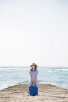 海岸でバッグを持って立つ女性
