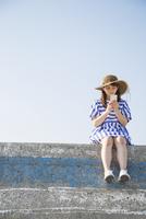 堤防に座ってスマートフォンを見る女性