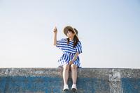 堤防に座ってスマートフォンで撮影する女性 11019033622| 写真素材・ストックフォト・画像・イラスト素材|アマナイメージズ