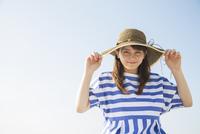青空と麦わら帽子をかぶった笑顔の女性
