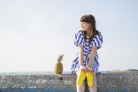 堤防に座る女性とパイナップル