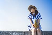 堤防にパイナップルを持って座る女性 11019033630| 写真素材・ストックフォト・画像・イラスト素材|アマナイメージズ