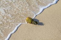 波打ち際に置かれたパイナップル