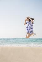 砂浜でジャンプする女性 11019033635| 写真素材・ストックフォト・画像・イラスト素材|アマナイメージズ