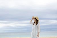 砂浜で遠くを見つめる女性