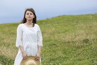 草原で麦わら帽子を持って立つ女性