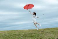 草原で傘を持ってジャンプする女性