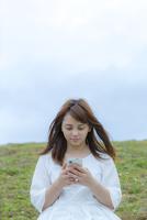 草原に座ってスマートフォンを見る女性