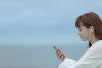 スマートフォンで音楽を聴く女性